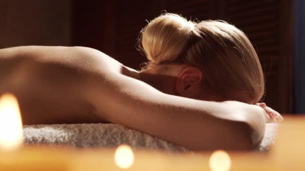 Mladá a krásná žena dostává masážní terapii v lázeňském salonu. Zdravý životní styl a koncepce péče o tělo.