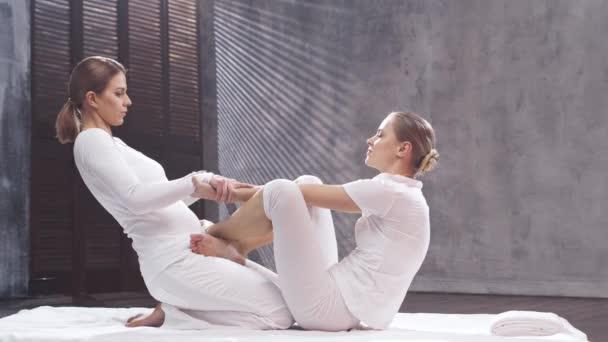 Junge Frau bekommt Thai-Massage-Behandlung durch Therapeuten. Traditionelle asiatische Stretchtherapie.