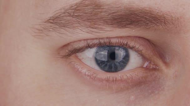 Detailní záběr mužského modrého oka. Muž se dívá do kamery zblízka. Makro duhovky, zornice a obočí. Poruchy zraku, oftalmologie a optometrie.