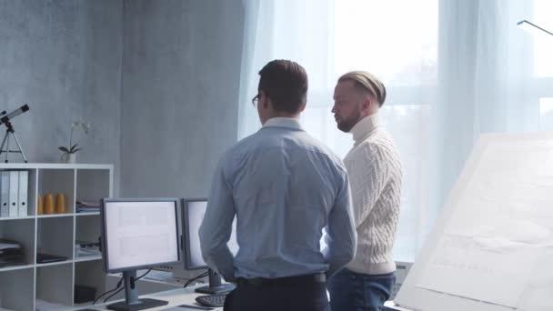 Architekt a jeho kolega pracují v podkroví pomocí kreslicích prken a počítačů. Pracoviště stavebního inženýra v moderní kanceláři. Koncept developmentu nemovitostí.