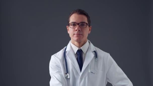 Studio portrét mladého profesionálního lékaře pracující s neviditelným obrazovým digitálním rozhraním přes šedé pozadí