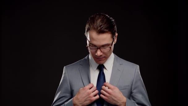 Stúdió portré sikeres és okos üzletemberről öltönyben és nyakkendőben. Férfi a formális kopás felett fekete háttér.