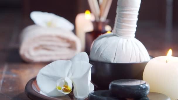 Spa zurück. Handtuch, Kerzen, Blumen, Massagesteine und Kräuterbälle. Massage, orientalische Therapie, Wohlbefinden und Meditation.