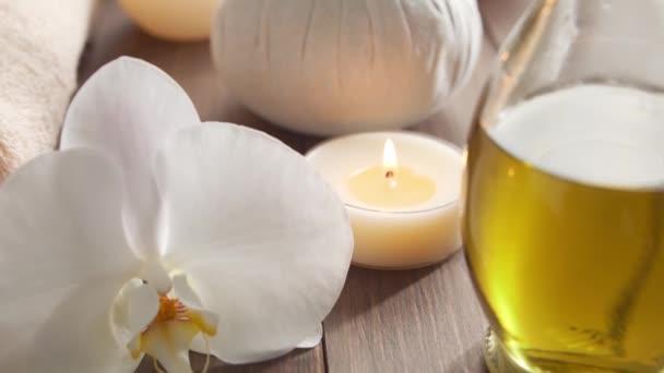 Lázeňské pozadí. Ručník, svíčky, květiny, masážní kameny a bylinné koule. Masáže, orientální terapie, pohoda a meditace.