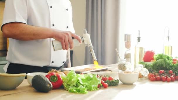 Mladý kuchař smaží lososa s plynovým hořákem v moderní kuchyni. Ten muž doma připravuje jídlo. Vaření zdravé jídlo.