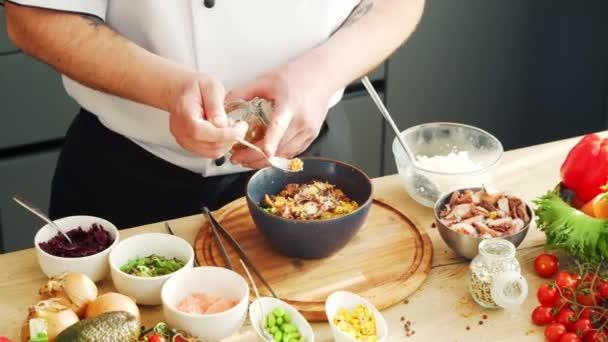 Young bereitet in einer modernen Küche eine Poke-Bowl zu. Der Mann bereitet zu Hause Essen zu. Gesundes Kochen.
