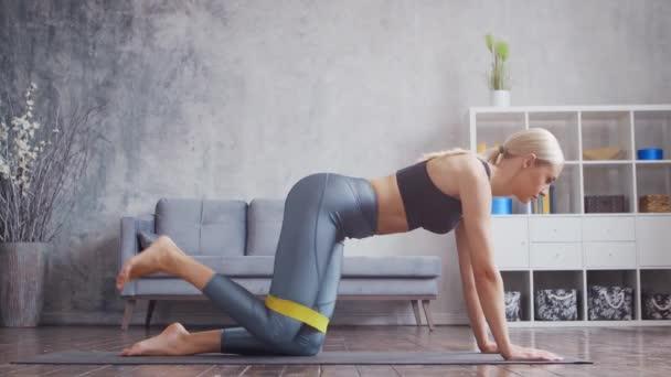 Fiatal és sportos lány a sportruházatban otthon gyakorolja az ellenállás sávját. Fitt és karcsú szőke nő megy be a sport és fitness. Egészségügyi, zsírégető és wellness.
