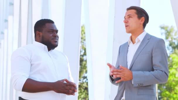 Magabiztos afro-amerikai üzletember és kollégája a modern irodaház előtt. A pénzügyi befektetők a szabadban beszélnek. Bankok és vállalkozások.
