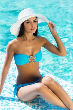 Young brunette woman in a swimsuit relaxing near the swimming pool