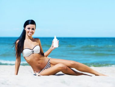 Sexy woman with a sun protection cream