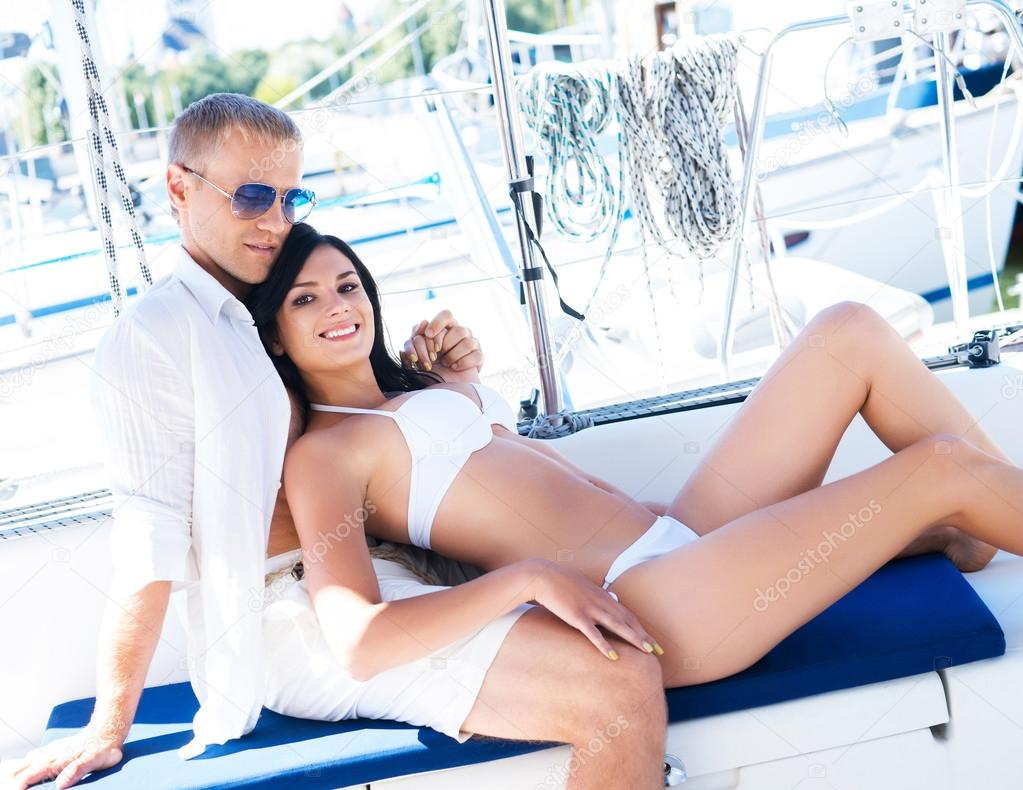 37968cc457 Handsome and rich man and a beautiful and sexy woman in swimsuit relaxing  on a sailing boat — Photo by ...