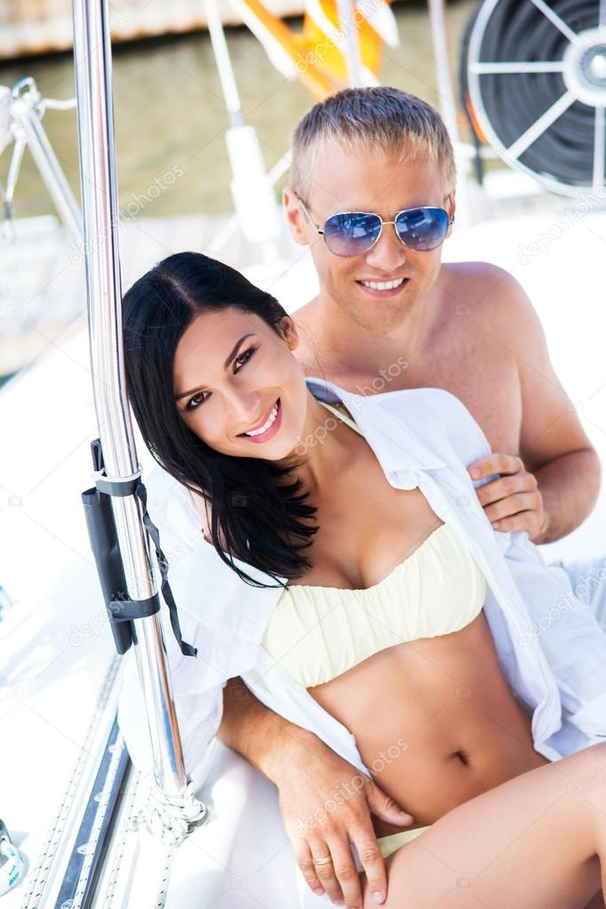 59a8af15b6 Handsome and rich man and a beautiful and sexy woman in swimsuit relaxing  on a sailing boat — Photo by shmeljov