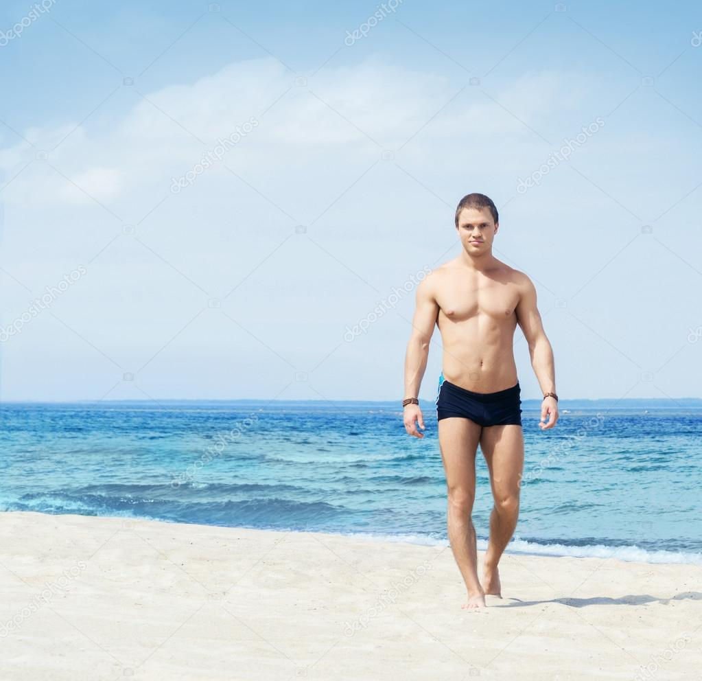 muscled and handsome man on beach