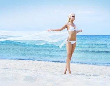 Woman posing with blowing silk on beach