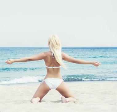 woman in swimsuit relaxing on beach