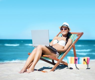 woman with laptop relaxing on beach