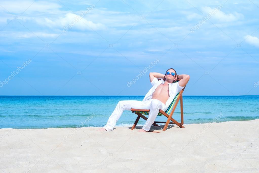 mann sitzt auf einem liegestuhl am strand stockfoto shmeljov 74701301. Black Bedroom Furniture Sets. Home Design Ideas
