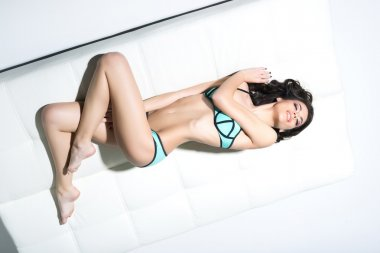 woman in swimsuit posing on  sofa