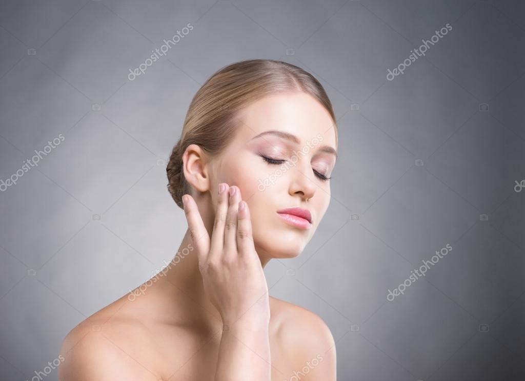 jolie fille de toucher sa peau lisse sur les joues sur fond gris photographie shmeljov 83377122. Black Bedroom Furniture Sets. Home Design Ideas