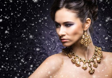 woman in jewel necklace and earrings