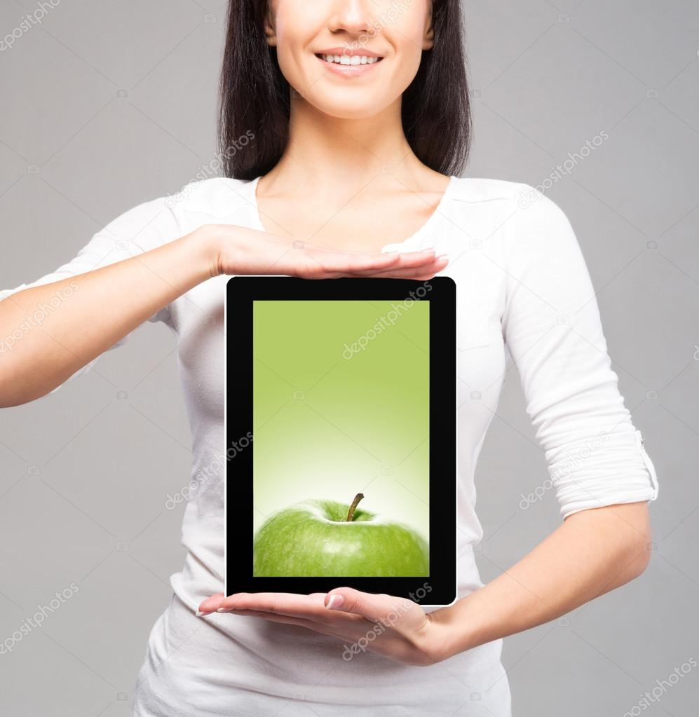 Young and beautiful teenager girl holding an ipad tablet