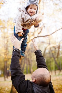 Father Playing with Son in the Autumn Park