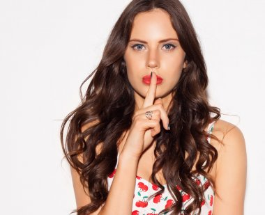 Portrait of beautiful young woman pointing finger to her lips over white background. Concept silent secret. Indoor. Close up.