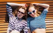 Close up lifestyle summer portrait of two girls friends relaxed and getting sunbathe, laying on the beach, wearing bright marine costumes and stylish sunglasses. Yacht. Sea, summer.