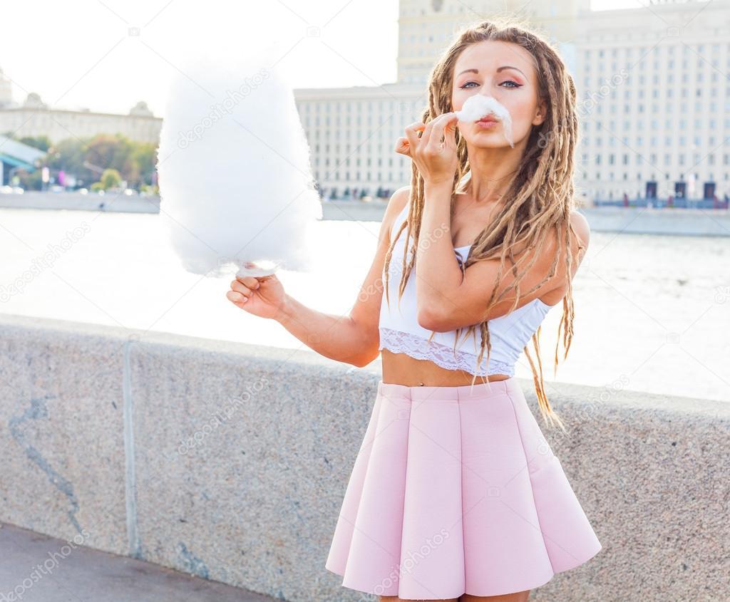 91cb7c6efd698e9 Красивые модные девушки едят хлопок конфеты весело провести время в теплый  летний вечер на берегу реки в центре города– Стоковое изображение