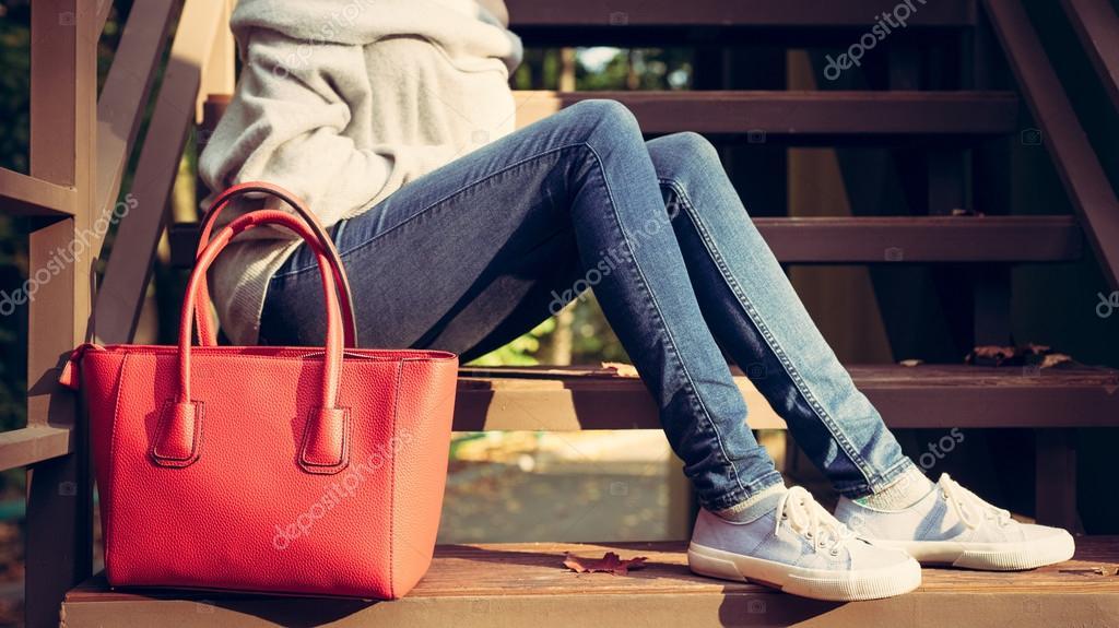 25d4b7647d276 Dziewczyna siedzi na schodach z duży czerwony super modne torebki w sweter  dżinsy i Adidasy na ciepły, letni wieczór. Ciepłe kolory– obraz stockowy
