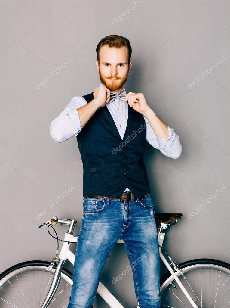 83871cd3a929 A young man with mustache and beard is near fashionable modern fixgear  bicycle. Jeans and shirt, vest and straightens the bow tie hipster style.
