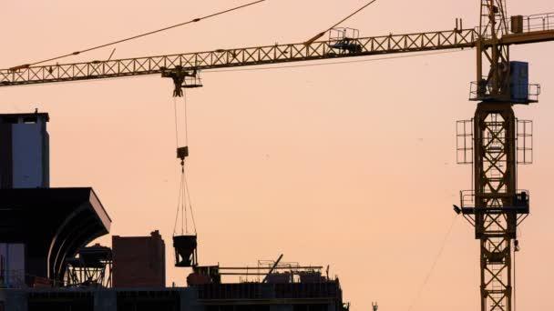 Kran hievt den Beton in die oberen Stockwerke eines neuen Hauses
