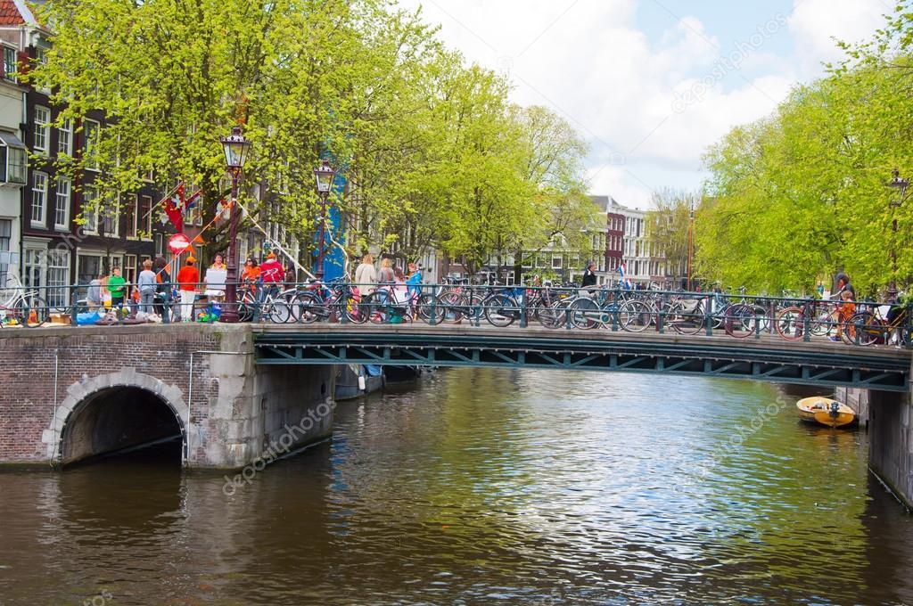 amsterdam canal de amsterdam con multitud de personas y bicicletas en el puente del rey el da los pases bajos u fotografa editorial