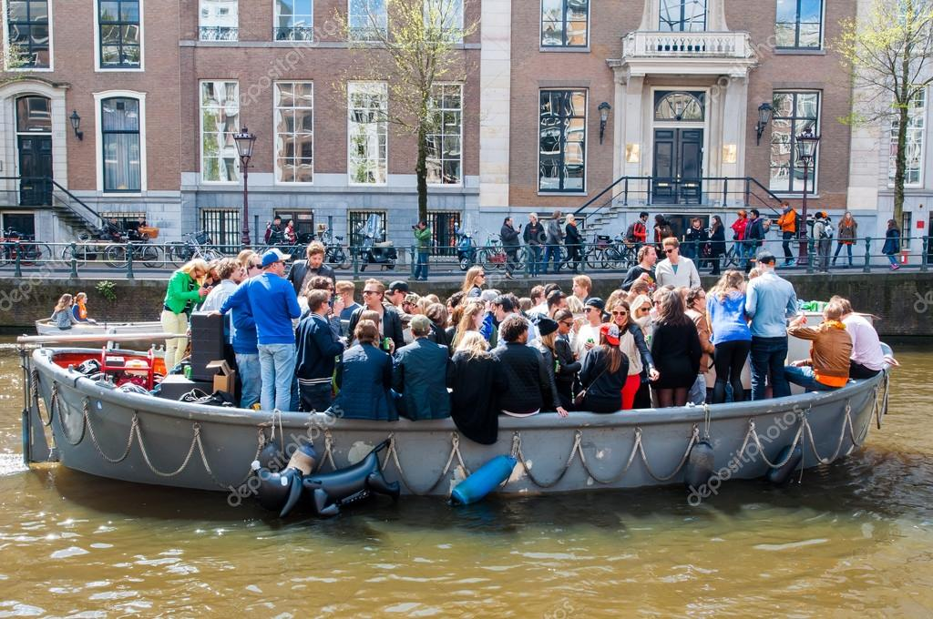 AMSTERDAM,NETHERLANDS-APRIL 27: Locals and tourists on Boat party through Amsterdam canals during King's Day on April 27,2015.