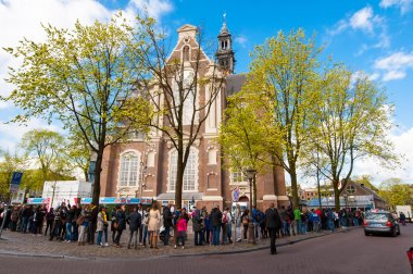 People stand in a queue to visit the Anne Frank House Museum in Amsterdam.