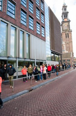 People  stand in line to visit the Anne Frank House Museum.