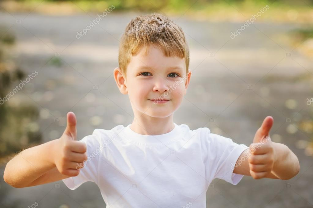Portrait of smiling boy holding his thumb up, horizontal image o