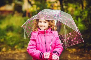Little girl hiding under an umbrella from the rain.