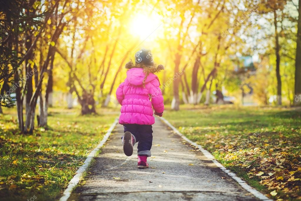 Little girl in a red jacket, running away the road in the autumn