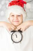Porträt eines glücklichen Kindes Weihnachten in Nikolausmütze hält Wecker clo