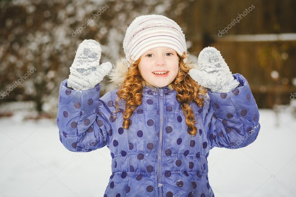 Little girl stretches her hand to catch falling snowflakes. Wint