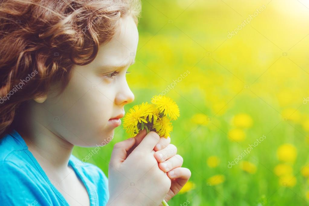 Little girl with yellow dandelions in the field. View profile.