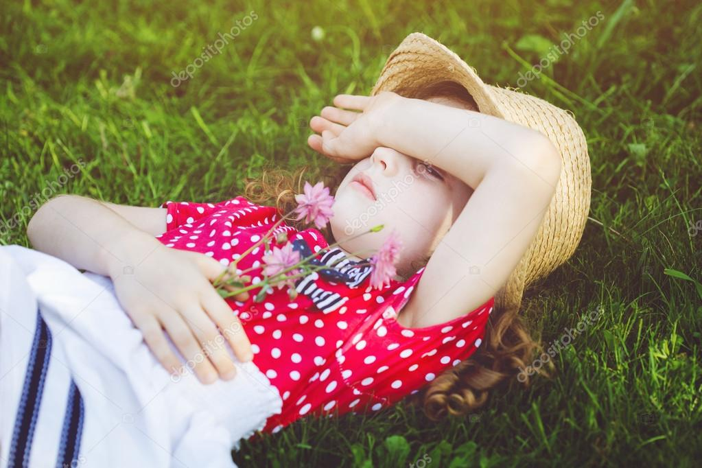 Offended little girl lies in the green grass and closed hands he