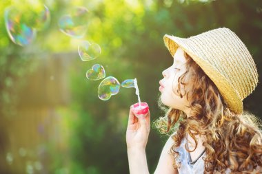 Cute girl blowing soap bubbles in a heart shape.