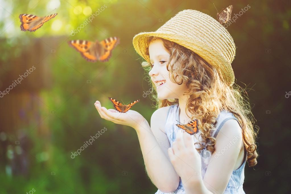 Laughing little girl with a butterfly on his hand. Happy childho