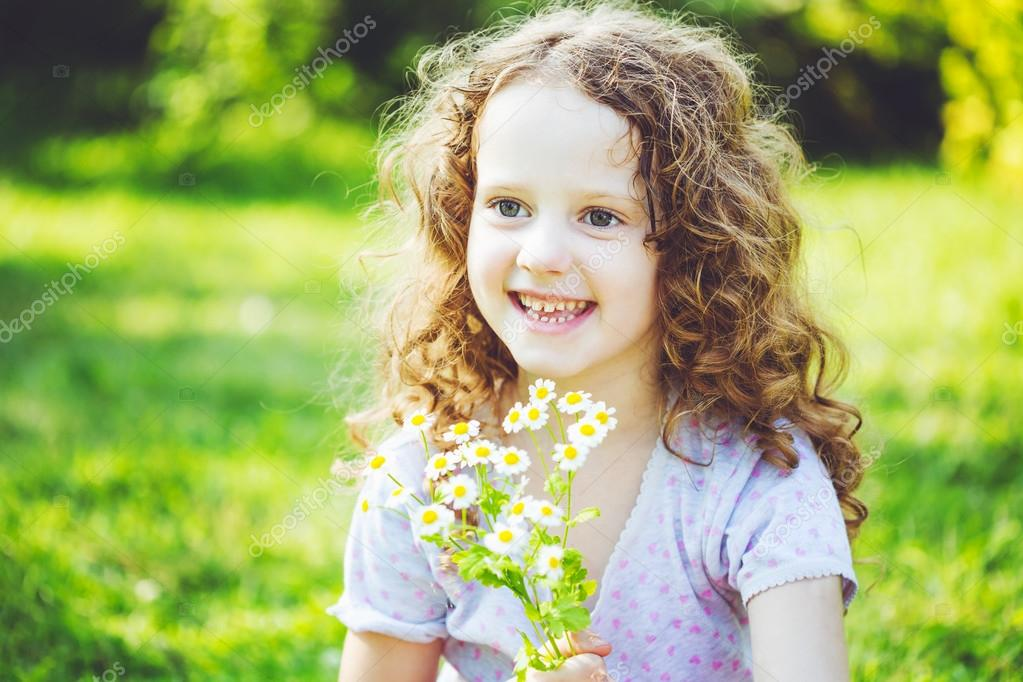 Smiling girl with a bouquet of white daisy. Mothers day concept.