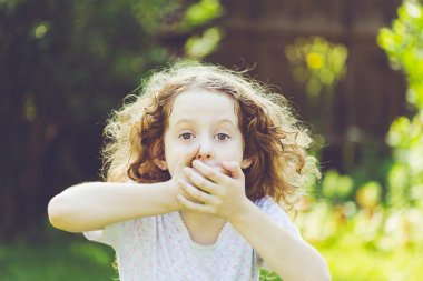 Little girl covering her mouth with her hands. Surprised or scared.