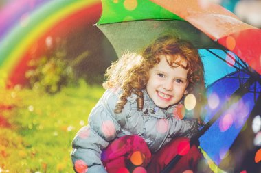 Laughing girl in the rain with a rainbow and with color bokeh.