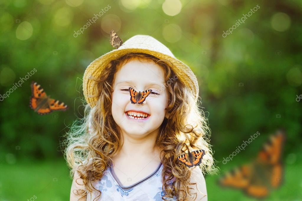 Laughing little girl with a butterfly on his nose.