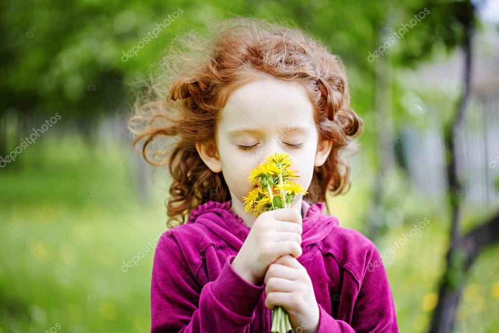 Little girl closed her eyes and breathes yellow dandelions in th